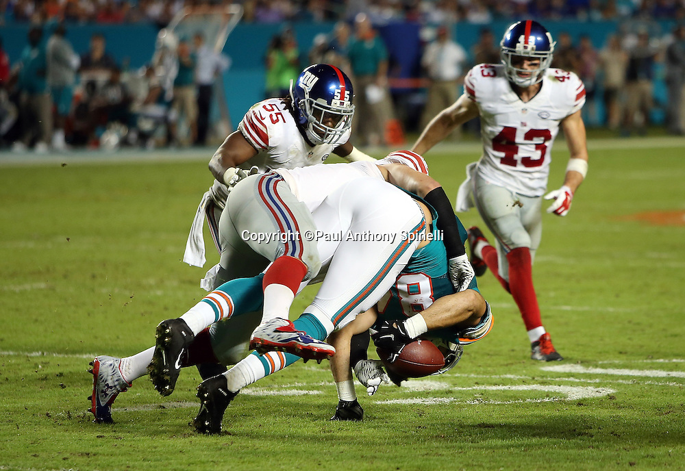 New York Giants outside linebacker Mark Herzlich (94) tackles Miami Dolphins tight end Jordan Cameron (84) causing an apparent fumble that was ruled not a fumble by the officials during the NFL week 14 regular season football game against the New York Giants on Monday, Dec. 14, 2015 in Miami Gardens, Fla. The Giants won the game 31-24. (©Paul Anthony Spinelli)