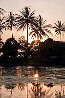 Sun setting through the palms over the sacred lake at Candidasa, Bali, Indonesia
