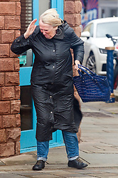 © Licensed to London News Pictures. 12/10/2018. Porthcawl, Bridgend, Wales, UK. People get buffeted by the gale force wind as Storm Callum hits the small Welsh seaside town of Porthcawl in Bridgend, UK. Photo credit: Graham M. Lawrence/LNP