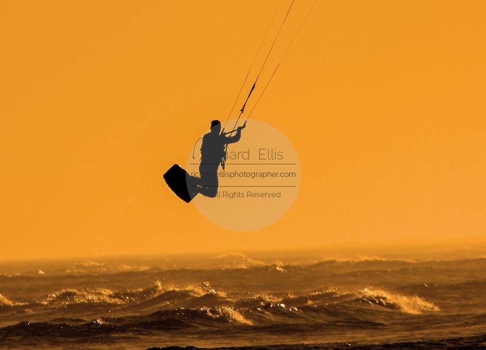 Kite boarder jumps into the air during sunset on Sullivan's Island, SC.