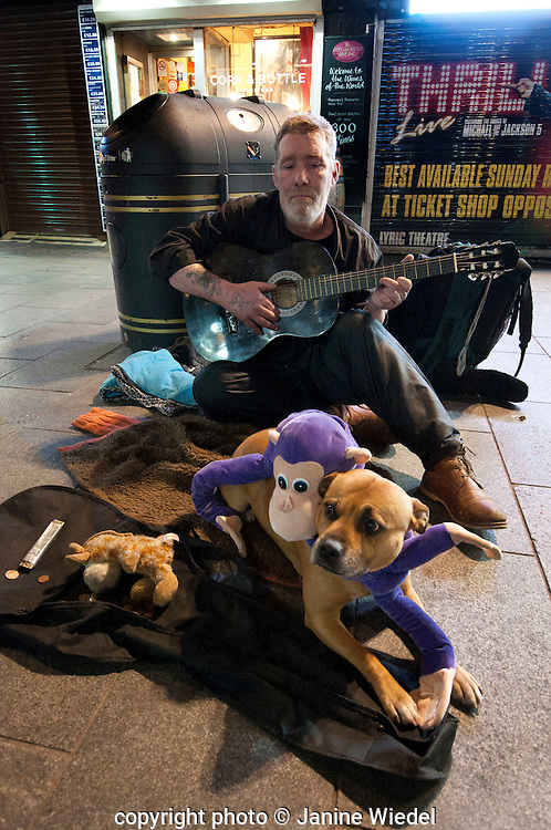 Homeless man busking and playing guitar in Soho with hia dog.