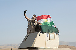 20/10/2016. Bashiqa, Iraq. A Kurdish peshmerga machine gunner takes a selfie with the Kurdish flag on the turret of his armoured Humvee as he takes part in a large offensive to retake the Bashiqa area from Islamic State militants today (20/10/2016).<br />