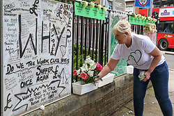 © Licensed to London News Pictures. 14/06/2019. London, UK. A woman places flowers to commemorate the second anniversary of the Grenfell Tower fire. On 14 June 2017, just before 1:00 am a fire broke out in the kitchen of the fourth floor flat at the 24-storey residential tower block in North Kensington, West London, which took the lives of 72 people. More than 70 others were injured and 223 people escaped. Photo credit: Dinendra Haria/LNP