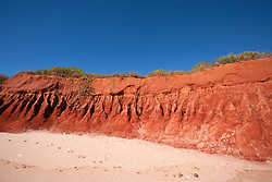 Stunning red pindan cliffs meet white sand at James Price Point