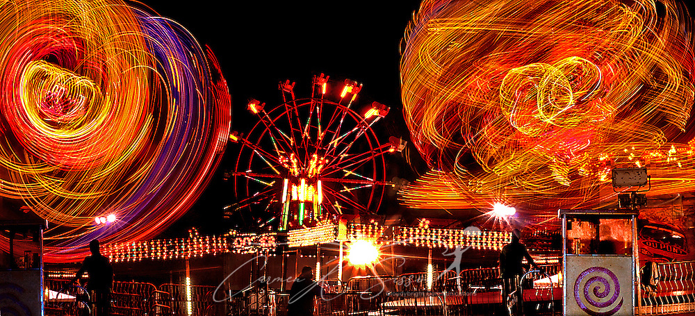 A composite image of workers watching as the Spin-Out ride at the West Alabama Exposition Fair lights up the sky over Munny Sokol Park in Tuscaloosa, Alabama. (Photo by Carmen K. Sisson/Cloudybright)