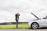 Sad young businessman standing with hands on head near broken car at countryside