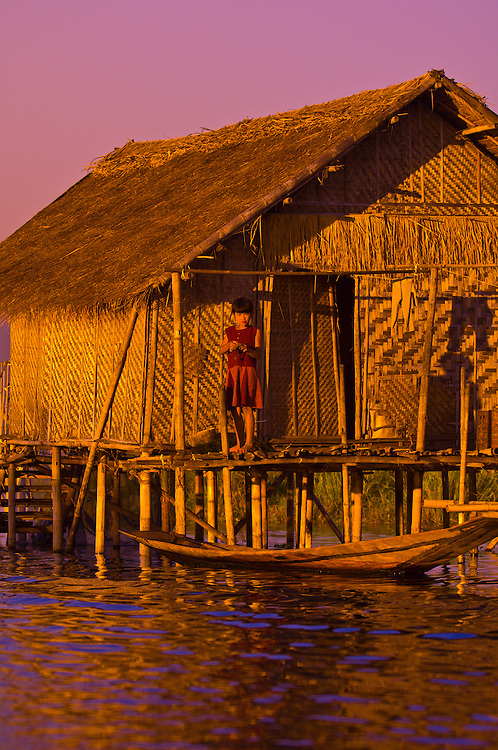 Girl standing outside house on stilts, Nampan, Inle Lake, Myanmar (Burma)