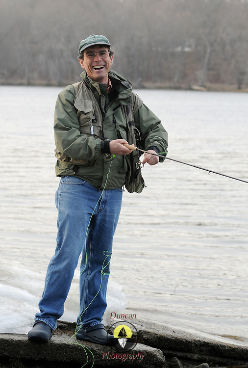 """Fly fishing coach Macauley Lord takes a break from teaching to smile at the camera on the banks of the Androscoggin River on Thursday afternoon. Lord, who is studying ministry at Bangor Theological Seminary says, """"chaplaincy is more like coaching than fishing.""""  He started coaching in 1986 -- but has fished since '68. Photo by Roger S. Duncan."""