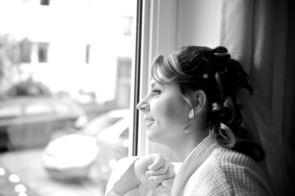 Die Braut sieht gespannt aus dem Fenster während sie auf den Chauffeur wartet, der sie zur Kirche fahren wird.