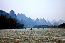 Early morning sun begins to penetrate the smog shrouding the karst mountain peaks along the River Li in the Yangshuo region of Southern China. Two-six person rafts, each  made of plastic piping and powered by an outboard motor, take tourists on a 90-minute, round-trip cruise from a small marina in Yangshuo.