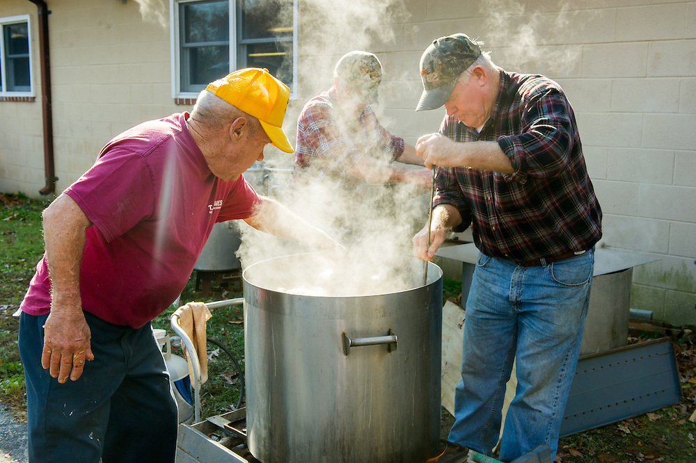 Men boiling stuffed hams outside, in large pans in St Mary's County, Maryland, USA
