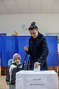 Mirela-Eleana Negoi with her son Denis voting the new president during the presidential elections at a polling station in Marginenii de Jos.