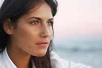 Pensive Woman on Beach looking out to sea head shot close up