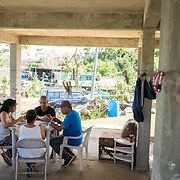 NOVEMBER 23 - TOA ALTA, PUERTO RICO - <br /> Thanksgiving meal in the garage of Nancy Ojeda's house  in the Comunidad Las Acerolas. From left; Michelle Vazquez Ojeda, 21, Nancy Ojeda, 62, back to camera, Angel Joel Alvarez, 34, and Max Ojeda, 59. The house has been without power since Hurricane Maria and it's sheltering several family members.<br /> (Photo by Angel Valentin/FREELANCE)