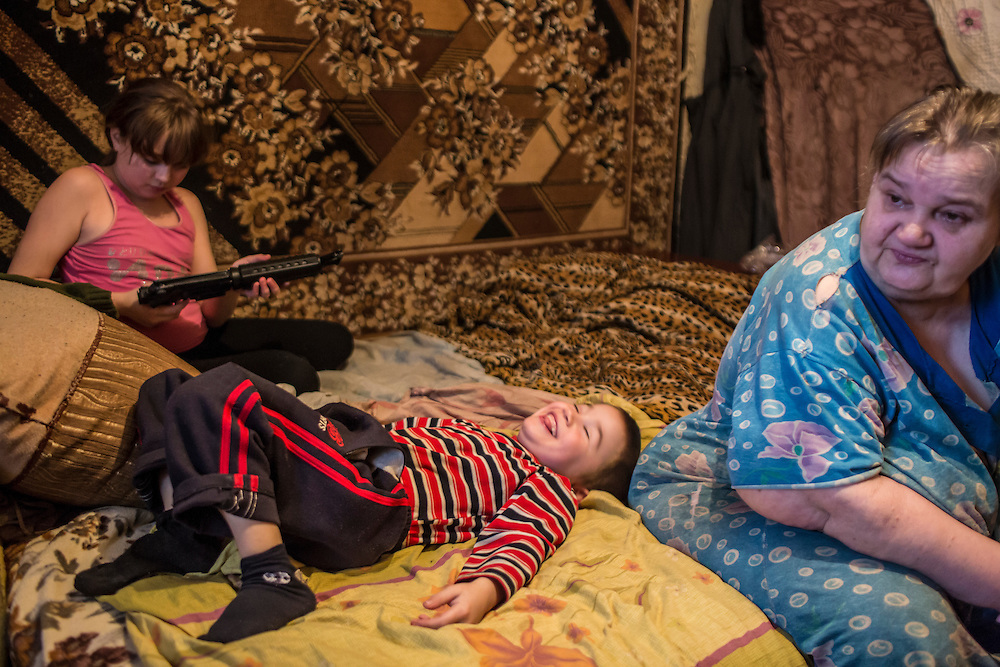 Lyuda, 10, and her cousin Nazar, 6, in the apartment where they live with their grandmother, at right, and two other cousins (not pictured) on Sunday, December 13, 2015 in Popasna, Ukraine. Nazar's mother, the daughter of the woman at right, was killed by shelling earlier in the year in Pervomaisk, a rebel-controlled city that saw very heavy fighting and where Nazar's father still lives.