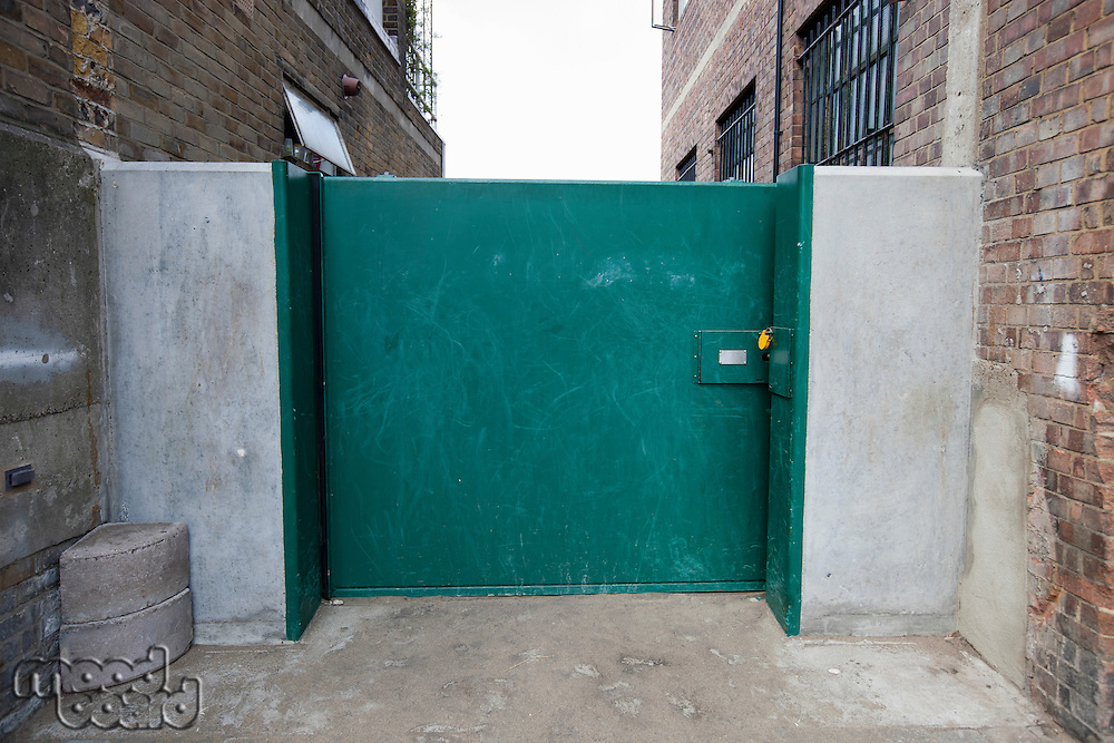 Closed green gate connected to buildings