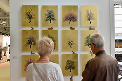 """© Licensed to London News Pictures. 27/06/2017. London, UK.  Visitors view """"Cornucopia"""" by Jack Frame at The Arts & Antiques Fair taking place at Olympia in Kensington.  The event is the UK's largest and most established art and antiques fair and runs until 2 July.   Photo credit : Stephen Chung/LNP"""