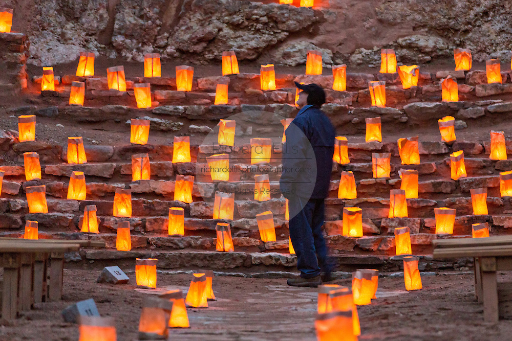 A man looks at the ruins of the San José de los Jémez Mission part of the Jemez Historic Site illuminated by hundreds of small paper lanterns known as luminaria to celebrate the holiday season December 12, 2015 in Jemez Springs, New Mexico. The site is in the Jémez Indian pueblo and contains an early 17th-century mission complex.
