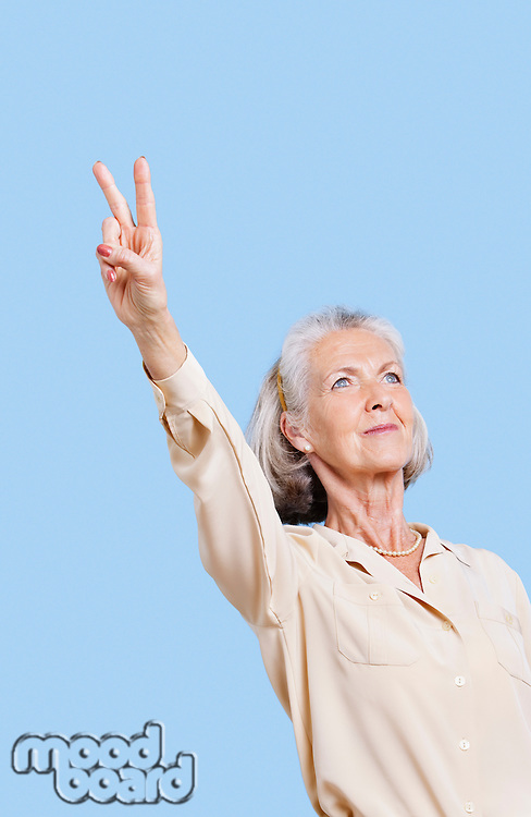 Senior woman in casuals gesturing peace sign against blue background