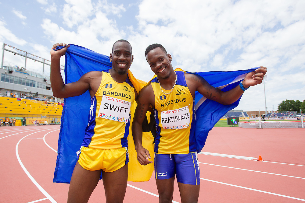 Bronze medalist Shane Brathwaite (R) and teammate and 4th place finisher Greggmar Swift  of the Barbados celebrate their runs in the final of the 110 metre hurdles at the 2015 Pan American Games at CIBC Athletics Stadium in Toronto, Canada, July 24,  2015. Both men set new personal bests and finished 0.07 seconds apart. AFP PHOTO/GEOFF ROBINS