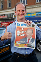 © Licensed to London News Pictures. 10/10/2014. Clacton, UK. Douglas Carswell, newly elected and first ever MP of UKIP for Clacton-on-Sea posing with a copy of Election Gazette as he visits at Clacton town centre on Friday, 10 October, 2014 after his victory in the by-election of Clacton-on-Sea. Photo credit : Tolga Akmen/LNP