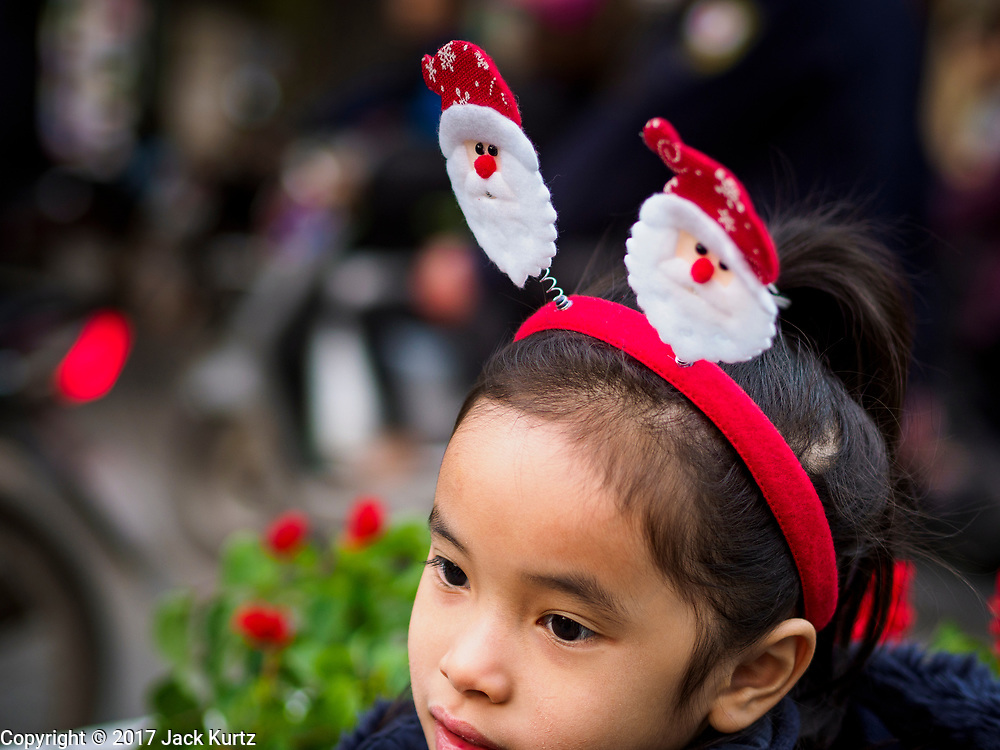 22 DECEMBER 2017 - HANOI, VIETNAM: A child wearing a Santa Claus headband before the Christmas show at St. Joseph's Cathedral in Hanoi. There are about 5.6 million Catholics in Vietnam. The Cathedral was one of the first structures built by the French during the colonial era and was opened in 1886. It's one of the most popular tourist attractions in Hanoi.      PHOTO BY JACK KURTZ