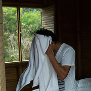 Antonio Cruz Sanchez dries his hair after his morning shower which follows his duties: feeding the chickens, dog, fish, and hydroponic system , watering the plants and preparing the filtered water in the SERES Embassy, his communal living space. San Juan Del Obispo, Guatemala, July 21, 2014