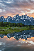The sun sets behind the Tetons from Schwabacher's Landing on the Snake River in Grand Teton National Park, Jackson Hole, Wyoming