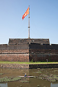 Flag Tower (Cot Co) flying the vietnamese flag above a man in canoe Hue Citadel / Imperial City, Hue, Vietnam