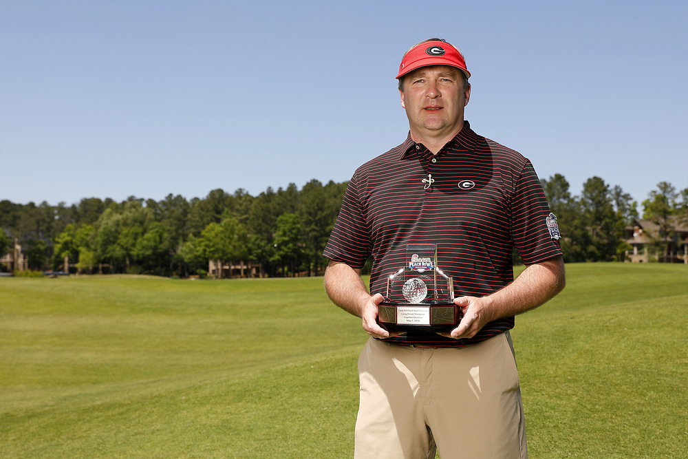 Kirby Smart poses with the Longest Drive trophy during the Chick-fil-A Peach Bowl Challenge at the Oconee Golf Course at Reynolds Plantation, Sunday, May 1, 2018, in Greensboro, Georgia. (Paul Abell via Abell Images for Chick-fil-A Peach Bowl Challenge)