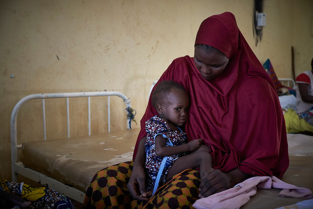 Hadiza Seini, 26 years old with her daughter Naima, 2 years old the centre for Treatment of Acute Malnutrition with Complications (CRENI) of the Poudriere Hospital, Niamey, Niger on February 16, 2016. Hadiza and Naima arrived that morning to the CRENI where they will rest until Naima is better. Poudri&egrave;re hospital is a reference hospital for the approximately 5 million people that live in the regions of Tilbery, Doss and Niamey with 581,000 children under 5 years. Constructed in 2002, it offers public health care, undertakes research and reinforces the capacity of medical staff. 37 doctors, 82 nurses and 22 midwives are employed at the hospital and have capacity of 146 beds with 72 of these in the paediatric section. Unicef supports the Therapeutic Nutritional Centre (TNC) for treating patients with severe acute malnutrition accompanied by complications (CRENI) which was rehabilitated in 2011 to treat 27 children. Since 2005, Unicef has supplied the hospital with ready-to-use therapeutic foods, medicine and training of healthcare workers.  In 2012, the last year of the nutrition crisis, 692 cases were treated with a recovery rate of 90%. <br /> <br /> <br /> &lsquo;My child had a fever, she was coughing and sores started forming around her mouth. I went to the Tallagu&eacute; health centre for a consultation and they gave her a syrup and tablets. Despite that, Naima&rsquo;s health did not improve and we were referred to come here.&rsquo;