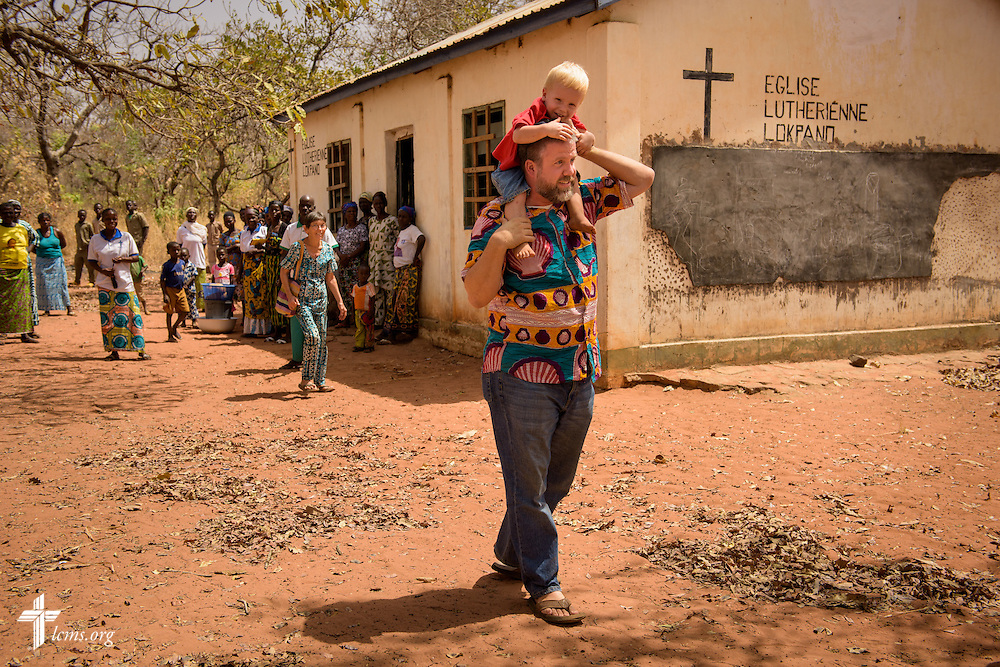 The Rev. Micah Wildauer, LCMS missionary to Togo, carries his son David following a visit to the Lutheran Church of Togo in Lokpano on Monday, Feb. 13, 2017, in Lokpano, Togo. LCMS Communications/Erik M. Lunsford