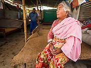 04 AUGUST 2015 - BUNGAMATI, NEPAL:  A woman sits on her bed in the temporary structure she shares with eight other families in Bungamati, a village about an hour from Kathmandu. Three months after the earthquake many families still live in tents and temporary shelters scattered around the village. The Nepal Earthquake on April 25, 2015, (also known as the Gorkha earthquake) killed more than 9,000 people and injured more than 23,000. It had a magnitude of 7.8. The epicenter was east of the district of Lamjung, and its hypocenter was at a depth of approximately 15km (9.3mi). It was the worst natural disaster to strike Nepal since the 1934 Nepal–Bihar earthquake. The earthquake triggered an avalanche on Mount Everest, killing at least 19. The earthquake also set off an avalanche in the Langtang valley, where 250 people were reported missing. Hundreds of thousands of people were made homeless with entire villages flattened across many districts of the country. Centuries-old buildings were destroyed at UNESCO World Heritage sites in the Kathmandu Valley, including some at the Kathmandu Durbar Square, the Patan Durbar Squar, the Bhaktapur Durbar Square, the Changu Narayan Temple and the Swayambhunath Stupa. Geophysicists and other experts had warned for decades that Nepal was vulnerable to a deadly earthquake, particularly because of its geology, urbanization, and architecture.    PHOTO BY JACK KURTZ