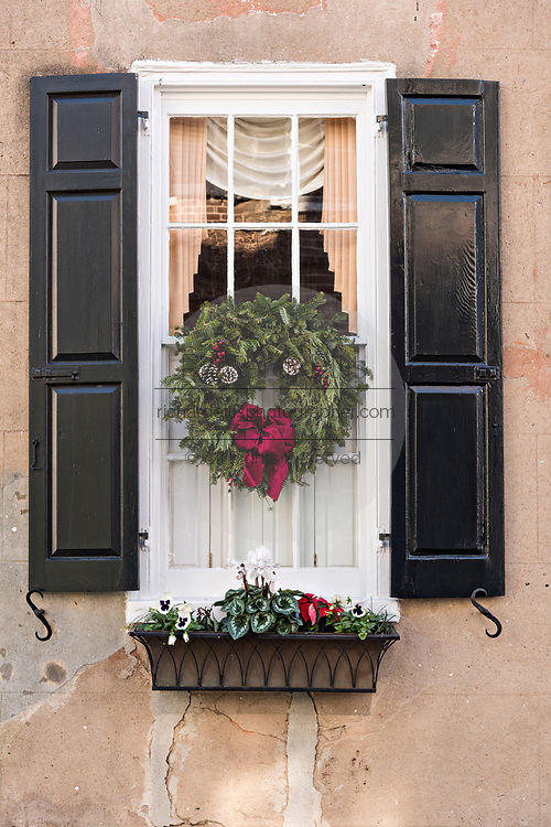 The window of a historic home decorated with a Christmas wreath and window box on Meeting Street in Charleston, SC.