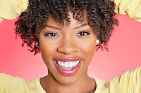 Close-up portrait of an African American woman smiling over colored background