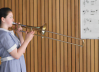 High school girl playing trombone in class side view