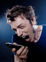 studio portrait on black background of a funny expressive caucasian man yelling at phone