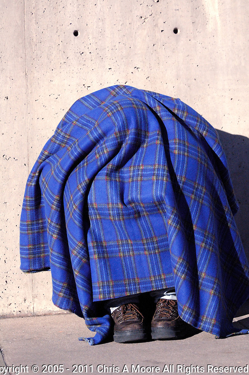 A homeless man huddles uunder the bright blue blanket at about 700 Lincoln Street in Denver.  By resting againgst the eastern wall of the parking garage, he is able to get the warmth of the sun on a cold January morning.