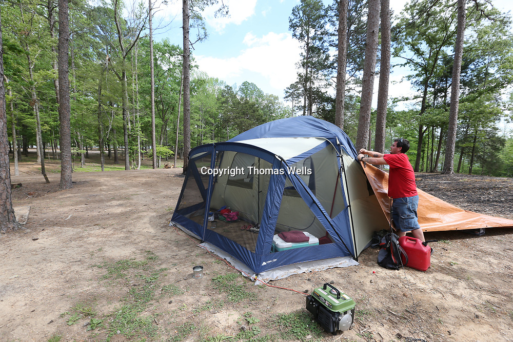 David Coe removes the cover from his tent after the high winds stopped blowing while he is staying at Chewalla Lake in Holly Springs.