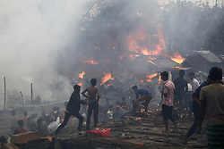 January 1, 2018 - Dhaka, Bangladesh - Bangladeshi fire Fighter and local people try to remove a fire broke out at Tejturi Bazar slum in Dhaka on January 1, 2018. Duty officer of Bangladeshi Fire Service and Civil Defense Russel said on information, nine firefighting units rushed to the spot and brought the flame under control around 1:20pm. (Credit Image: © Mehedi Hasan/NurPhoto via ZUMA Press)