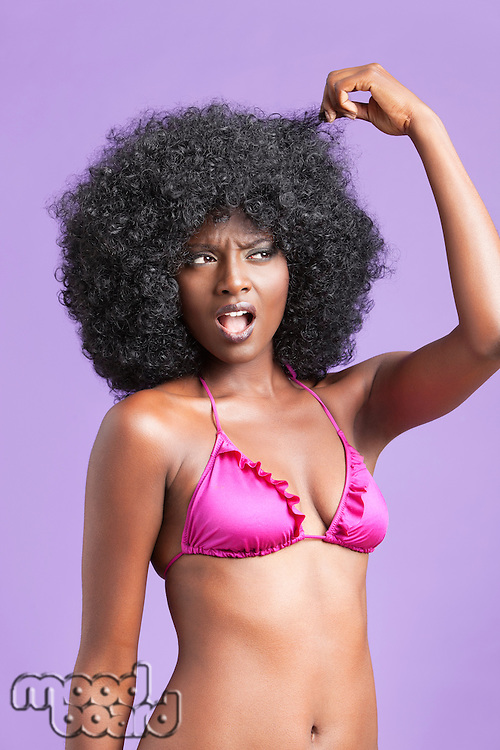 Surprised young woman in bikini touching her fizzy hair over violet background