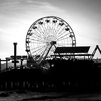 Santa Monica Ferris Wheel black and white photo. Santa Monica Pier is a Southern California landmark that has an amusement park with a ferris wheel, roller coaster, restaurants, and other attractions.