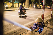 A man sleeps on a makeshift hammock along a quite Hanoi street in the evening, Vietnam, Southeast Asia