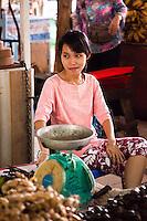 Female market vendor sitting at her stall.