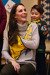 A cub scout uses a neckerchief to show the Duchess of Cambridge how to support a broken arm during a Cub Scout Pack meeting with cubs from the Kings Lynn District, in Kings Lynn at the The Scout and Guide Hut in North Wootton, near King's Lynn, for an event to celebrate 00 years of the Cub Scout movement.
