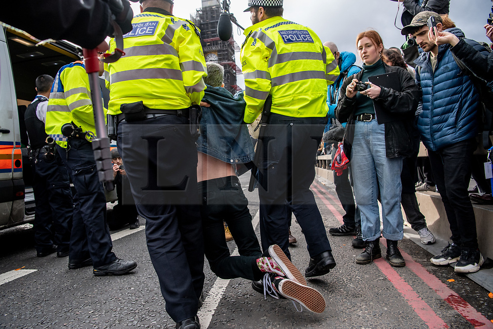 © Licensed to London News Pictures. 15/03/2019. London, UK. A student is arrested by police on Westminster Bridge.  School children across the UK took part in an international day of action protesting inaction over climate change. An 'after party' was held on Westminster Bridge, blocking traffic for several hours.  Photo credit: Guilhem Baker/LNP