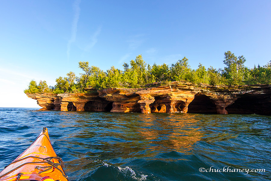 Kayaker exploring the sea caves of Devils Island in the Apostle Islands National Lakeshore, Wisconsin, USA model released