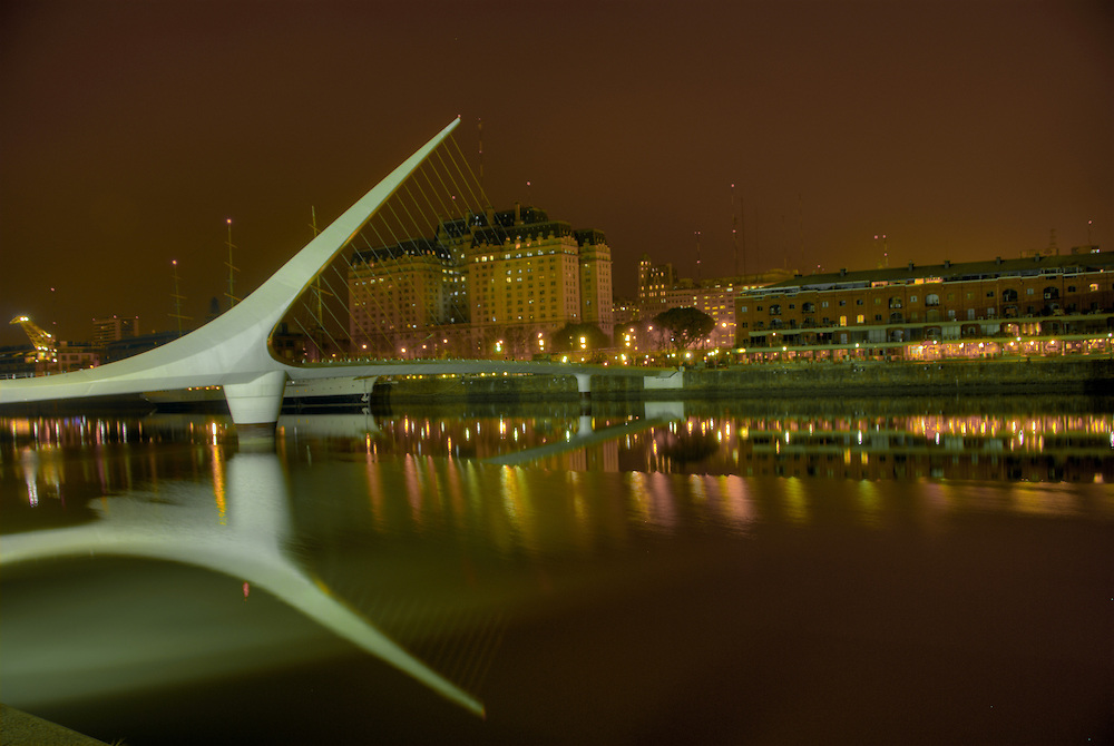 """Bridge """"La Mujer"""" in Puerto Madero, Buenos Aires, with view of the docks and recycled buildings. The Bridge was designed by Santiago Calatrava and its a Landmark on this tourist destination in Buenos Aires."""