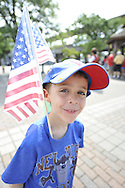 Smiling boy with American flag attends the Independence Day annual reading of the Declaration of Independence on Wednesday, July 4, 2012, held by Historical Society of the Merricks, Long Island, New York, USA. Volunteers each read one line from the historic document in this Long Island tradition.
