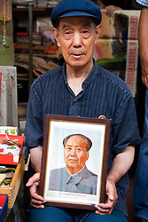 Man displaying portrait of Chairman Mao at famous Panjiayuan antiques market in Beijing